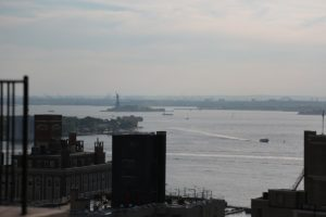 A view of the water and the statue of liberty in the distance